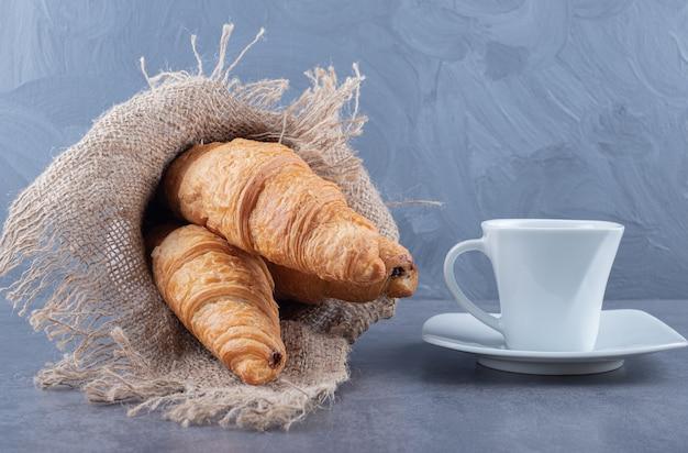 Zwei frische französische croissants mit kaffee auf grauem hintergrund.