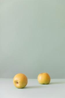 Zwei frische gelbe äpfel auf einem grünen hintergrund
