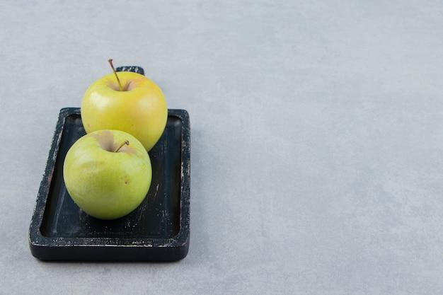 Zwei frische grüne äpfel auf schwarzem teller.