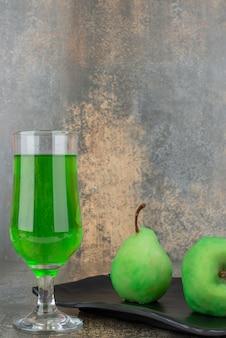 Zwei frische grüne äpfel mit glas grünem wasser auf dunklem teller