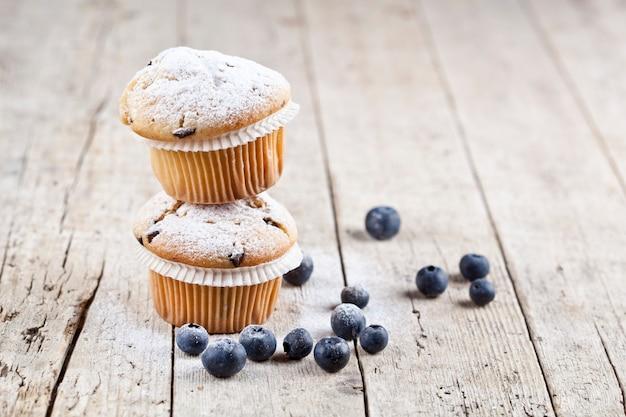 Zwei frische hausgemachte muffins mit heidelbeeren.