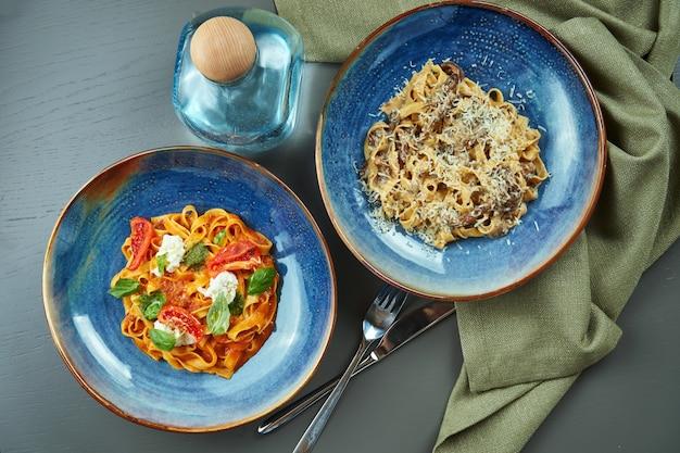 Zwei frische, hausgemachte nudeln mit waldpilzen und bolognese mit tomaten in einer blauen schüssel auf einem holztisch. draufsicht, flach liegen