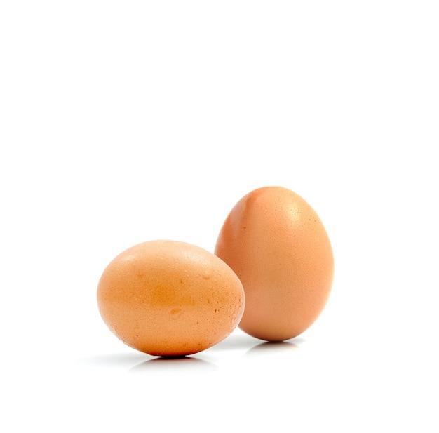 Zwei frische hühnereier getrennt gegen einen weißen hintergrund.