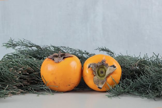 Zwei frische kakis auf weihnachtsbaumzweigen.