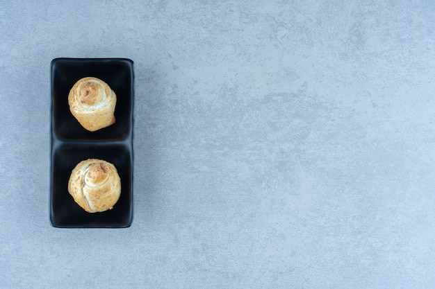 Zwei frische kekse auf schwarzem teller über grauem hintergrund.