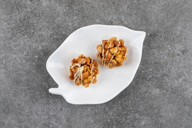 Zwei frische kekse mit erdnuss auf weißem teller über grauer oberfläche