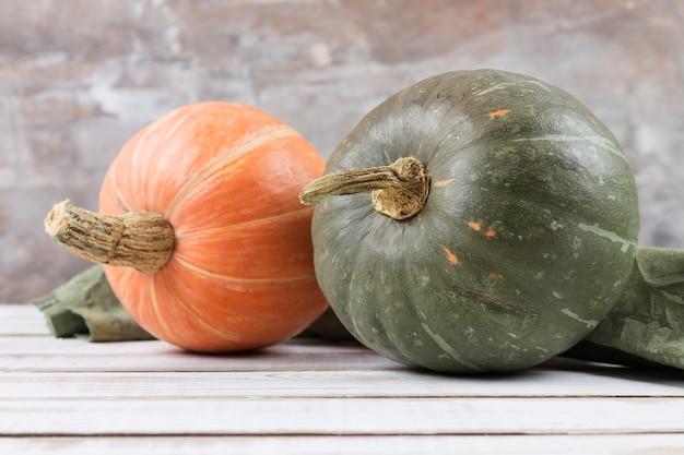 Zwei frische kürbisse, orange und grün, auf einem weißen holztisch. veganes essen