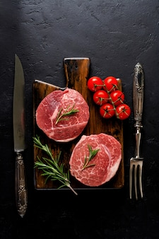 Zwei frische parisienne rohes steak auf weißem pergamentpapier mit salz, pfeffer und rosmarin im rustikalen stil auf altem steinhintergrund. schwarzer angus. ansicht von oben.