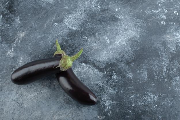 Zwei frische reife auberginen auf grauer hintergrundoberansicht.