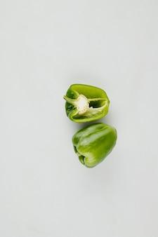 Zwei frische reife grüne paprikaschoten für salat oder suppe auf hellgrüner tischoberfläche
