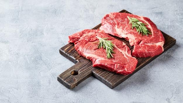 Zwei frische rohe fleisch prime black angus beef steaks, rib eye, denver, auf holzschneidebrett. tplace für text.