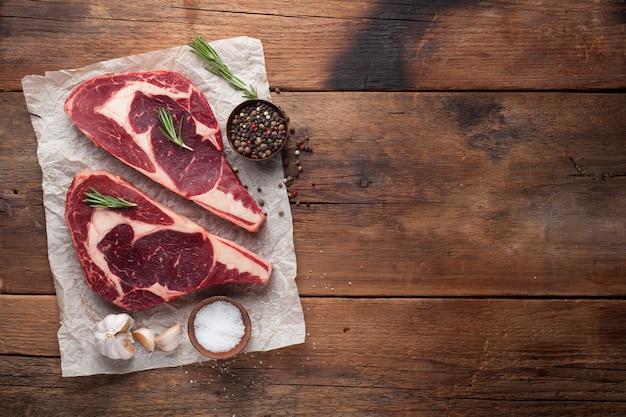Zwei frische rohe marmor ribeye steak mit gewürzen.