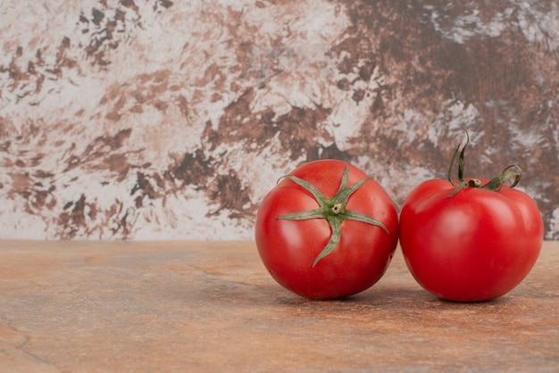 Zwei frische tomaten lokalisiert auf marmortisch.
