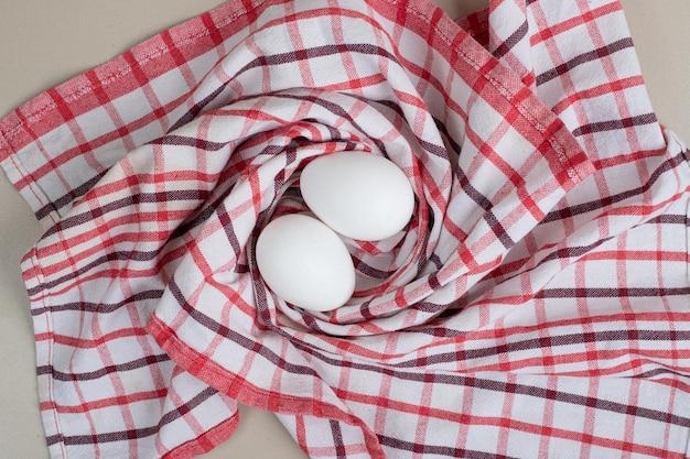 Zwei frische weiße hühnereier auf tischdecke.