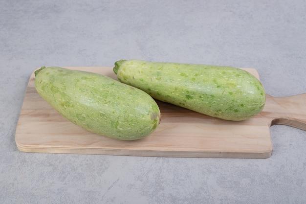 Zwei frische zucchini auf holzbrett. hochwertiges foto