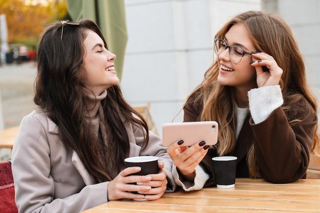 Zwei fröhliche, attraktive freundinnen, die draußen im café sitzen und beim kaffeetrinken auf das handy schauen