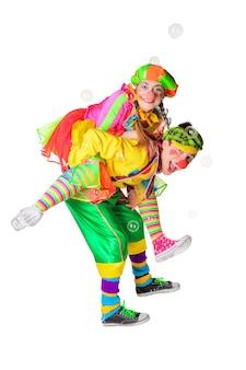 Zwei fröhliche clowns freuen sich über die seifenblasen auf weißem hintergrund