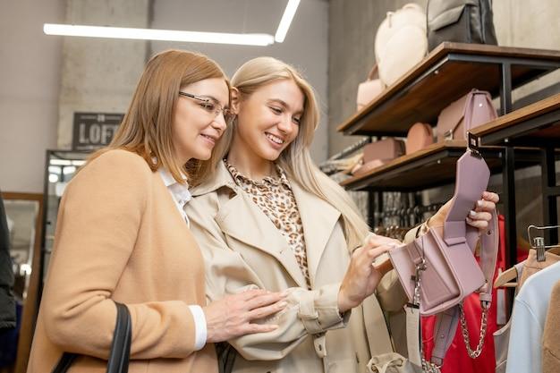 Zwei fröhliche frauen in schicker freizeitkleidung wählen handtaschen für die neue saison, während sie in der boutique neben dem regal mit rucksäcken und taschen stehen