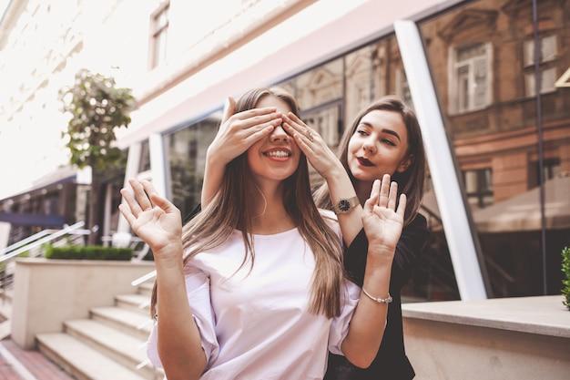Zwei fröhliche freundinnen, die spaß auf einer stadtstraße haben