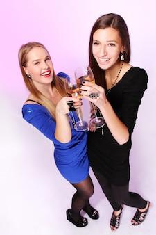 Zwei fröhliche freundinnen mit bunten cocktails