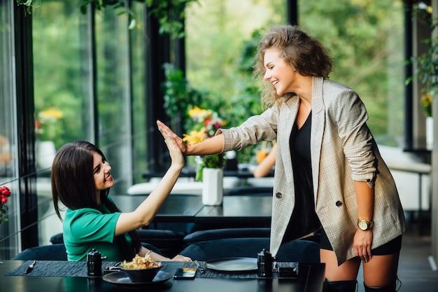 Zwei fröhliche, fröhliche freundinnen oder geschäftspartner, die sich beim mittagessen im fischrestaurant amüsieren?