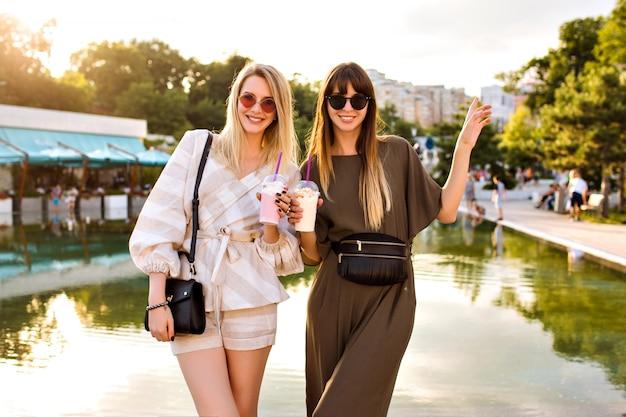Zwei fröhliche hübsche paare beste freundinnen, die auf stadtpark bei europa aufwerfen, leckere milchshakes trinken, die sommertag genießen