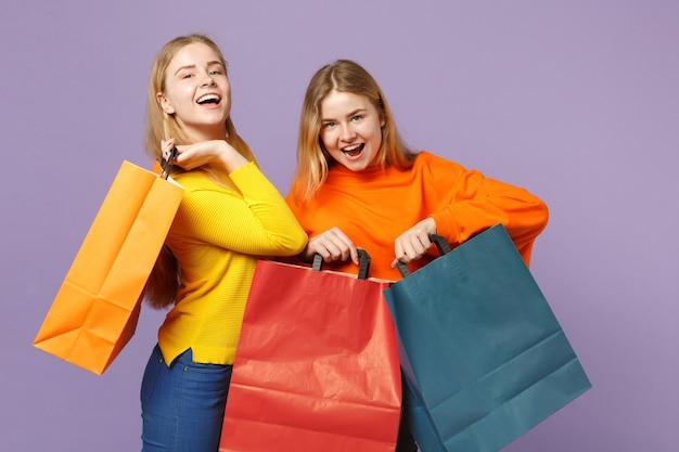 Zwei fröhliche junge blonde zwillingsschwestern mädchen in lebendiger kleidung halten pakettasche mit einkäufen nach dem einkaufen isoliert auf violettblauer wand. menschen-familien-lifestyle-konzept.