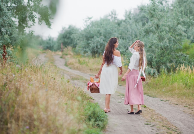 Zwei fröhliche junge frauen in retro-kleidung gehen mit einem picknickkorb den treppenabsatz entlang und unterhalten sich.
