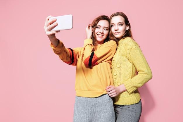 Zwei fröhliche junge frauen sprechen selfie