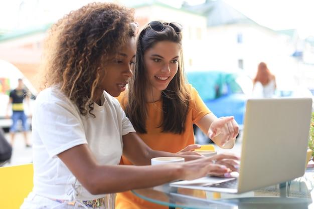 Zwei fröhliche junge freundinnen sitzen im café, haben spaß zusammen, trinken kaffee und benutzen laptop.