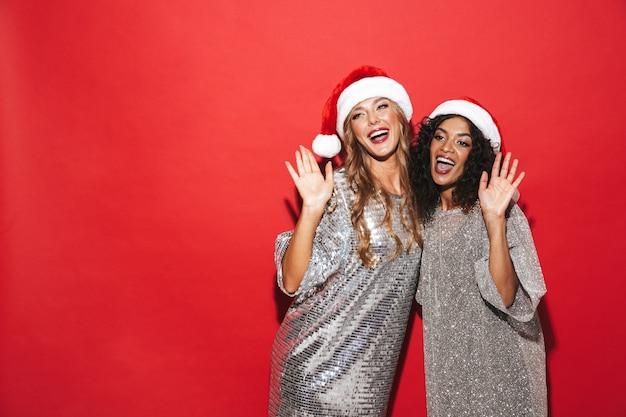 Zwei fröhliche junge klug gekleidete frauen, die neujahr feiern, lokalisiert über rotem raum