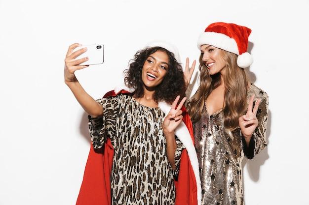 Zwei fröhliche junge klug gekleidete frauen, die neujahr feiern, lokalisiert über weißem raum