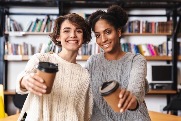 Zwei fröhliche junge mädchenstudenten, die an der bibliothek studieren und kaffee trinken