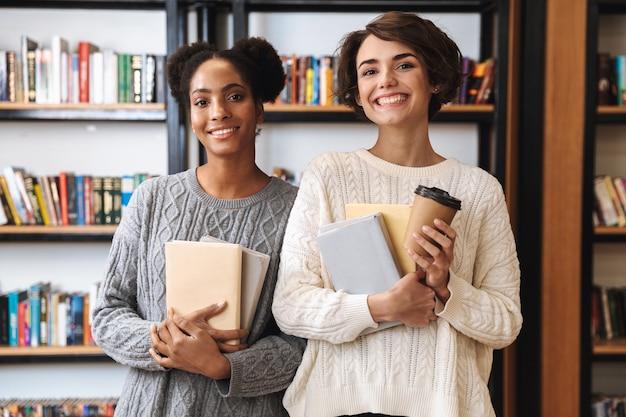 Zwei fröhliche junge mädchenstudenten, die an der bibliothek studieren