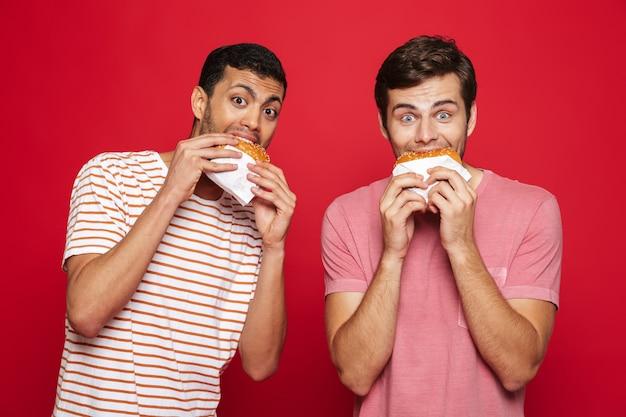 Zwei fröhliche junge männer, die isoliert über roter wand stehen und burger essen