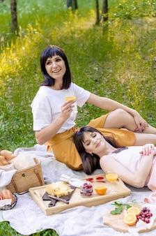 Zwei fröhliche junge modische frauen, die picknick am sonnigen tag haben