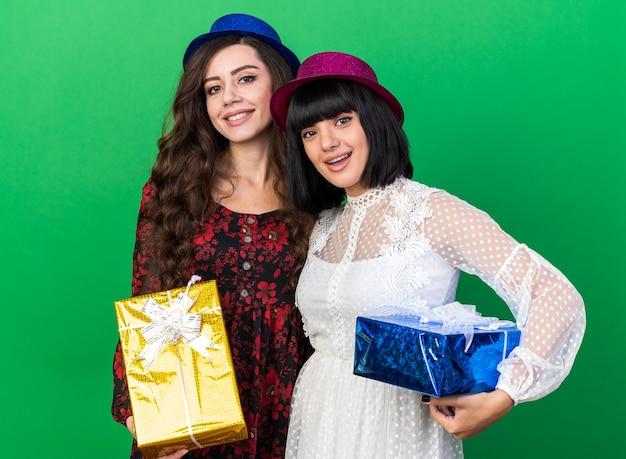 Zwei fröhliche junge partygirls mit partyhut, die beide ein geschenkpaket isoliert auf grüner wand halten