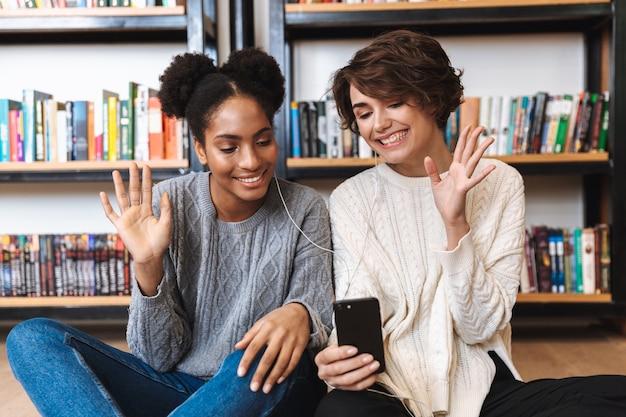 Zwei fröhliche junge studentinnen, die an der bibliothek studieren, musik mit kopfhörern hören, handy halten