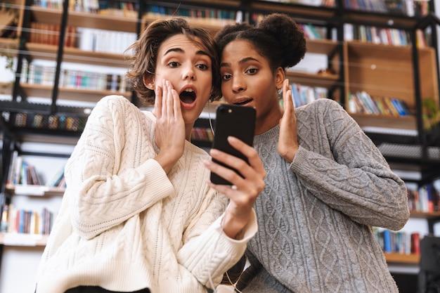 Zwei fröhliche junge studentinnen, die in der bibliothek studieren, mit dem mobiltelefon kopfhörer tragen