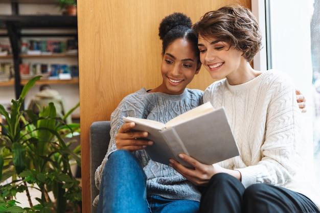 Zwei fröhliche junge studentinnen, die in der bibliothek studieren und gemeinsam ein buch lesen