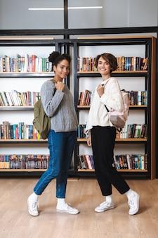 Zwei fröhliche junge studentinnen, die in der bibliothek studieren und rucksäcke tragen