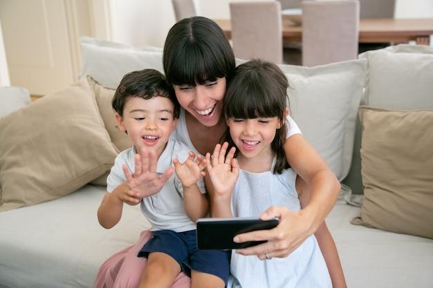 Zwei fröhliche kinder und ihre glückliche mutter, die telefon für videoanruf benutzen, während sie zusammen auf der couch zu hause sitzen