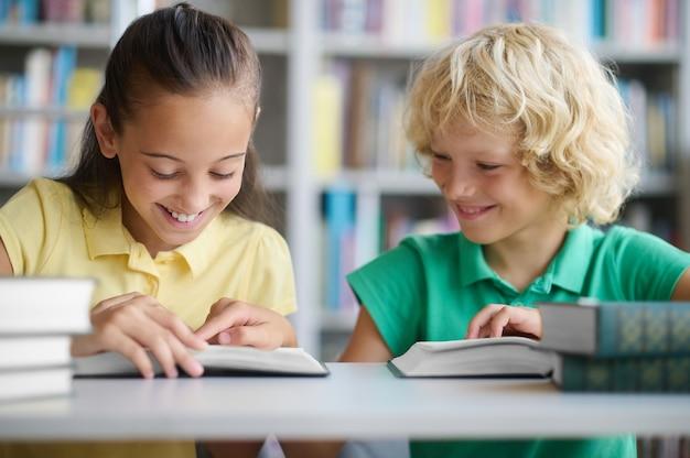 Zwei fröhliche klassenkameraden, die zusammen in einer öffentlichen bibliothek studieren