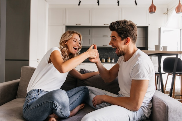 Zwei fröhliche leute, die auf sofa sitzen und auf daumen spielen. der mann sieht überrascht aus und sein freund sieht sehr glücklich und bereit zu gewinnen.