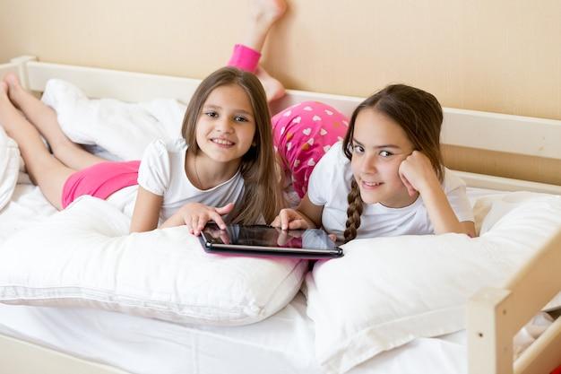 Zwei fröhliche mädchen im teenageralter liegen auf dem bett und benutzen tablet