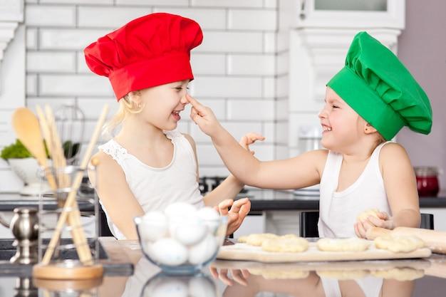 Zwei fröhliche mädchen kochen in farbigen kappen teig