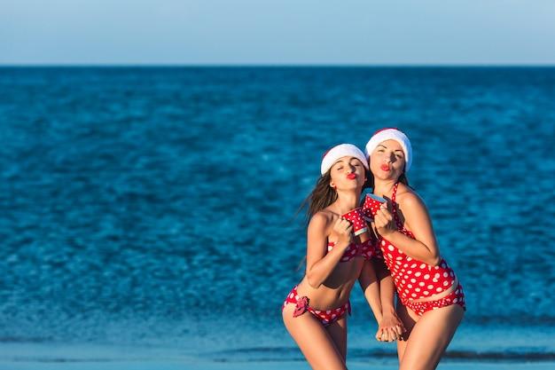 Zwei fröhliche mädchen, weihnachtlich gekleidet und mit tassen in der hand, schicken dir einen kuss. sommer-weihnachtsferien am meeresstrand.