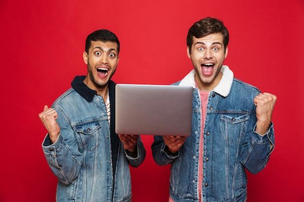 Zwei fröhliche männerfreunde, die isoliert über roter wand stehen, laptop-computer halten, feiern