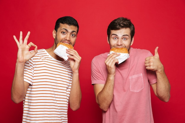Zwei fröhliche männerfreunde, die isoliert über roter wand stehen und burger essen
