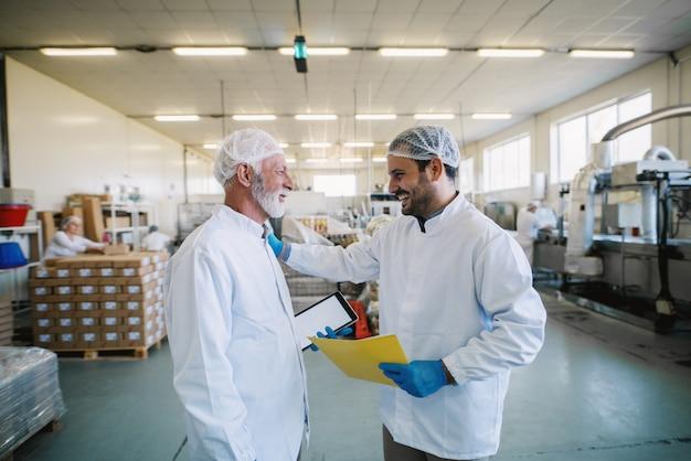Zwei fröhliche männliche lebensmittelfabrikangestellte in sterilen kleidern, die lächeln und über geschäftspläne sprechen.